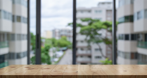 Empty wood table top and blur glass window wall building banner background Premium Photo