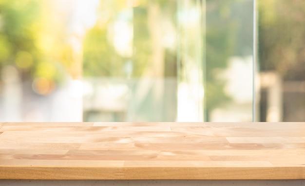 Пустая деревянная столешница на размытом абстрактном оконном стекле. для демонстрации продукта или дизайна ключевого визуального макета Premium Фотографии