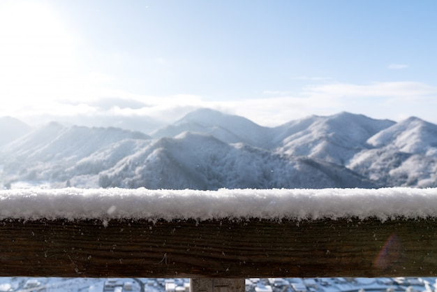 Empty wooden board top table in front of blurred snow mountain view Premium Photo