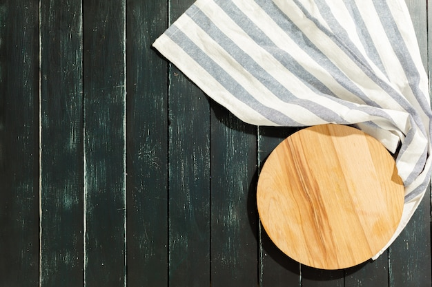 Empty wooden board with tablecloth on dark desk Premium Photo