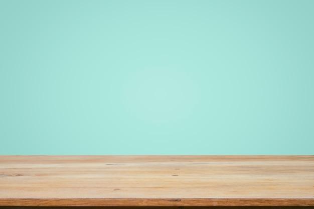 Empty wooden deck table over mint wallpaper background. Premium Photo