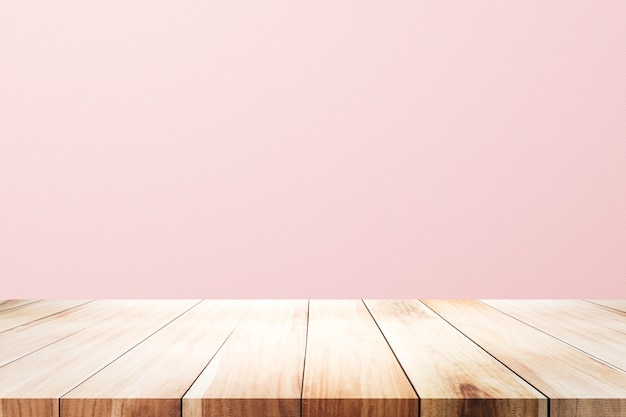 Empty wooden deck table over rusty pink background for present product. Premium Photo