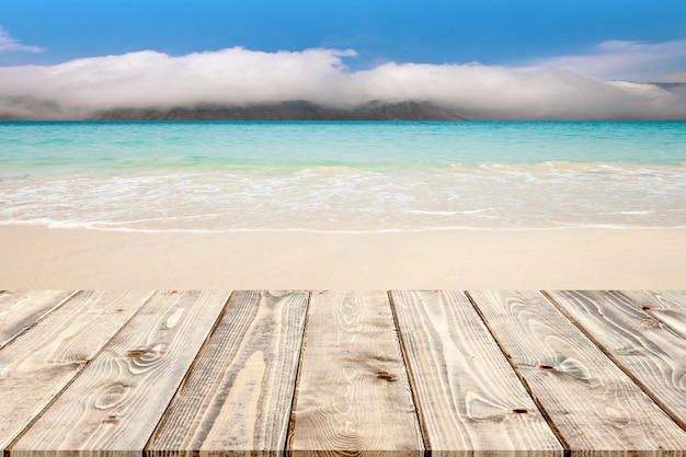 Empty wooden floor on tropical white sand beach and foggy mountain background. Premium Photo
