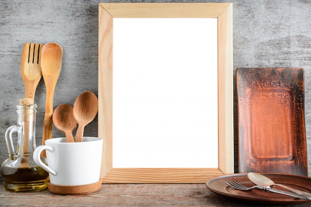 Empty wooden frame and kitchen accessories on the table Premium Photo