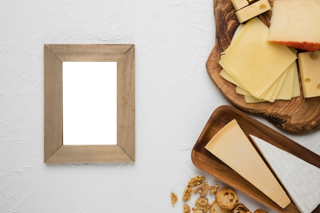 Empty wooden frame with cheese platter and ingredient on white surface Free Photo