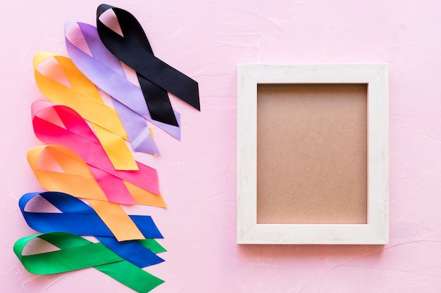 An empty wooden frame with colorful awareness ribbon on pink background Free Photo