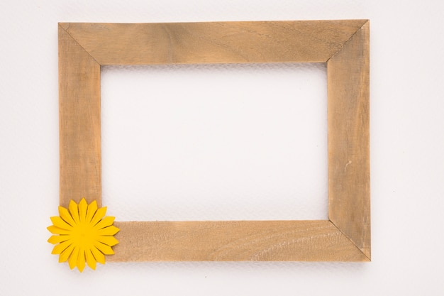 Empty wooden frame with yellow flower against white backdrop Free Photo