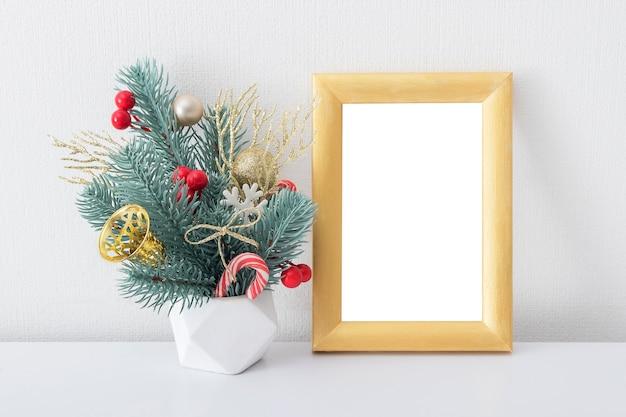 Пустая деревянная золотая рамка макет с рождественским букетом в интерьере белой комнаты Premium Фотографии