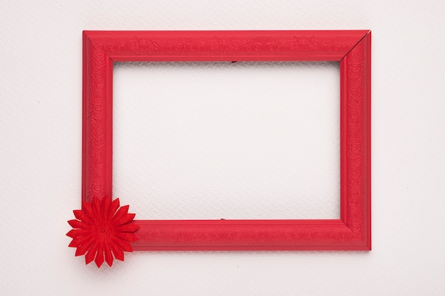 An empty wooden red border with flower on white wall Free Photo