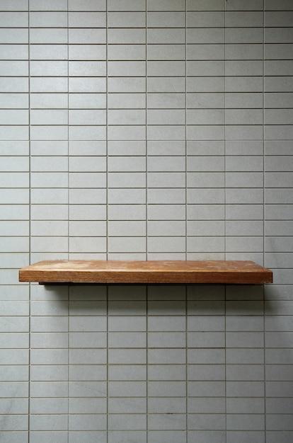 Empty wooden shelf on the tile wall. Premium Photo