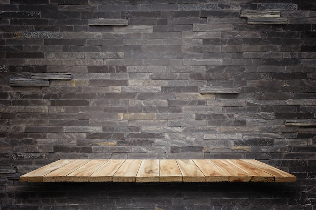 Empty wooden shelves and stone wall background. for product display Premium Photo
