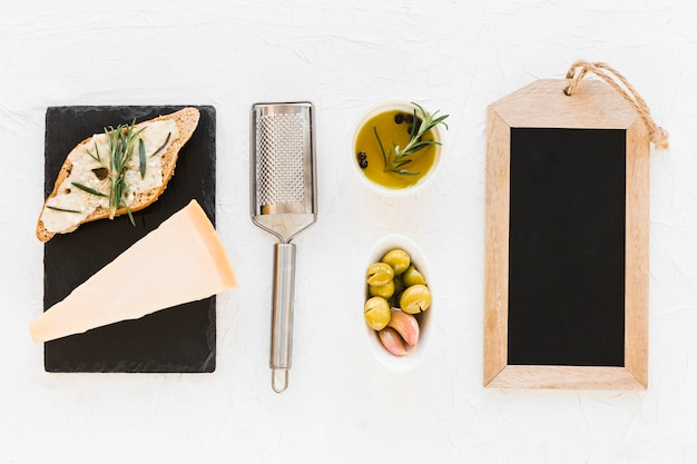 Empty wooden slate frame with olive and cheese on white background Free Photo