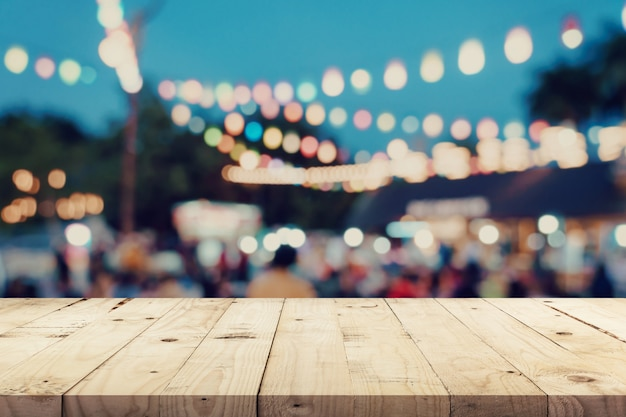 Empty wooden table and blurred background at night market Premium Photo