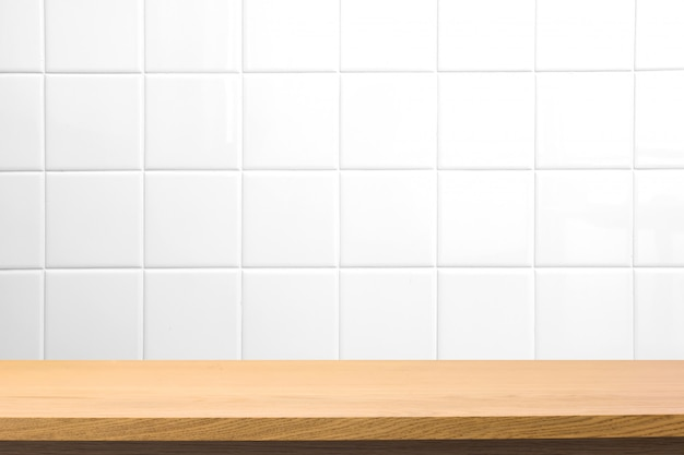Empty wooden table over blurred square ceramic tile wall Premium Photo