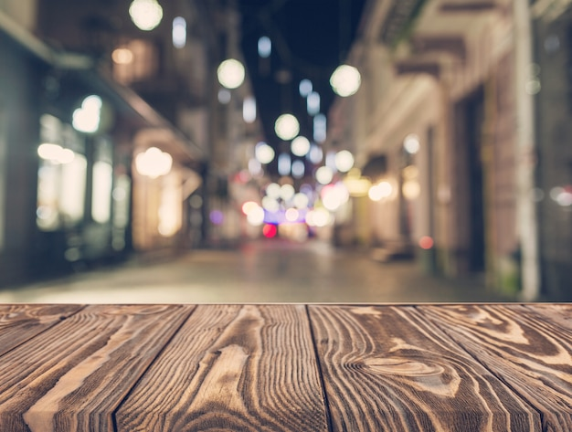 Empty wooden table in front of abstract blurred street background Free Photo