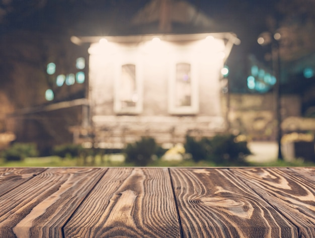 Empty wooden table in front of blurred house backdrop Free Photo