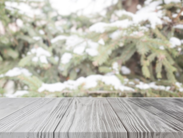 Empty wooden table in front of christmas tree with snow Free Photo
