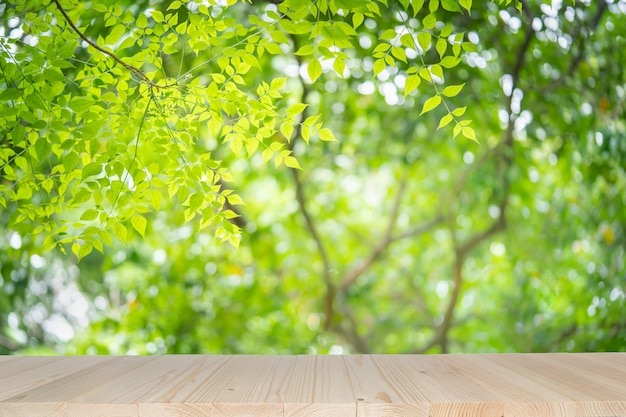 Empty wooden table on green nature background with beauty bokeh under sunlight. Premium Photo