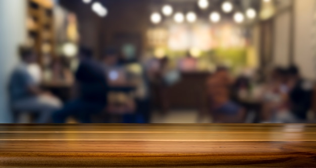 Empty wooden table for present product on coffee shop or soft drink bar blur background with bokeh image.