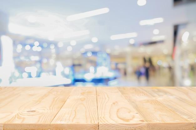 Пустая деревянная платформа для стола с размытым торговым центром или фоном торгового центра для монтажа дисплея продукта. деревянный стол с копией пространства. Бесплатные Фотографии