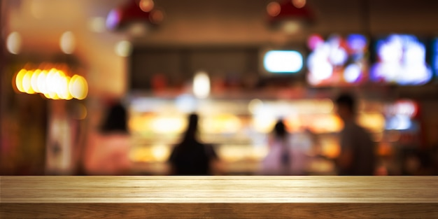 Empty wooden table top with blur coffee shop or restaurant interior background. Premium Photo
