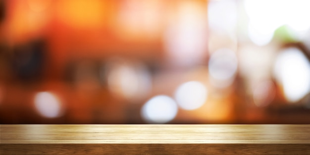 Empty wooden table top with blur coffee shop or restaurant interior background Premium Photo