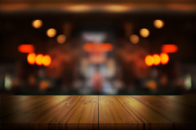 Empty wooden table top with blurred coffee shop. Premium Photo