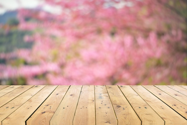 Empty wooden table top with colorful floral blurred background Premium Photo