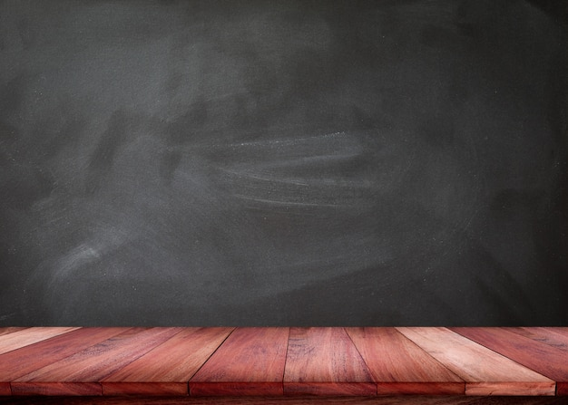Empty wooden table with blackboard texture Premium Photo
