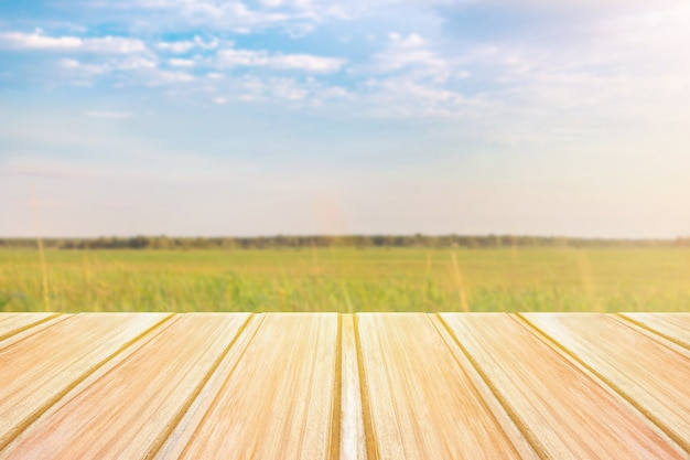 Empty wooden table with blurred green field on background and blue sky Premium Photo