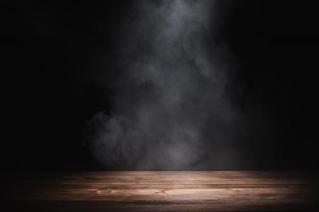 연기와 함께 빈 나무 테이블은 어두운 배경에 떠 프리미엄 사진