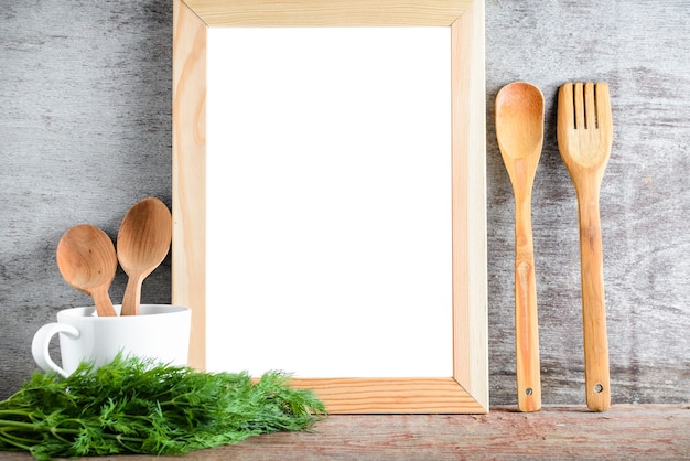 Empty wooden white isolated frame and kitchen accessories on a wooden table. Premium Photo