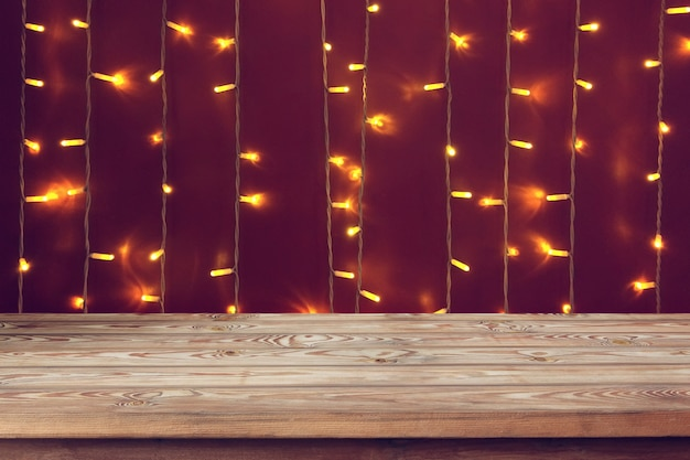 Empty wooden worktop on the christmas lights. Premium Photo