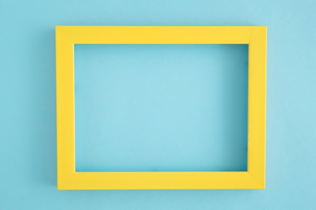 An empty yellow border frame on blue background Free Photo