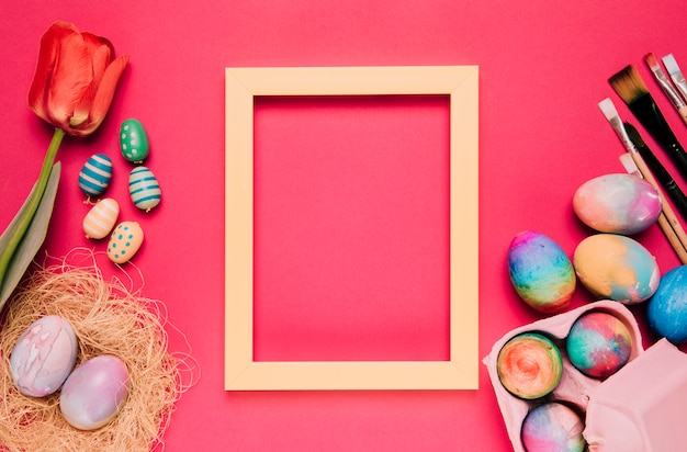 An empty yellow border frame with colorful easter eggs; paint brushes; tulip on pink backdrop Free Photo