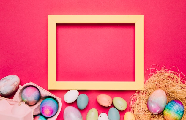 An empty yellow frame with colorful easter eggs on pink background Free Photo