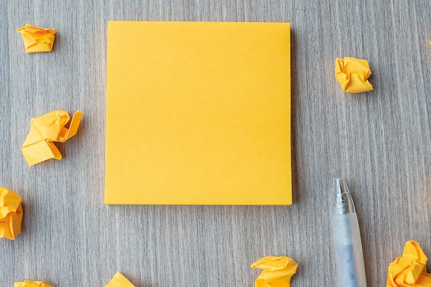 Empty yellow note paper with pen and crumbled paper Premium Photo