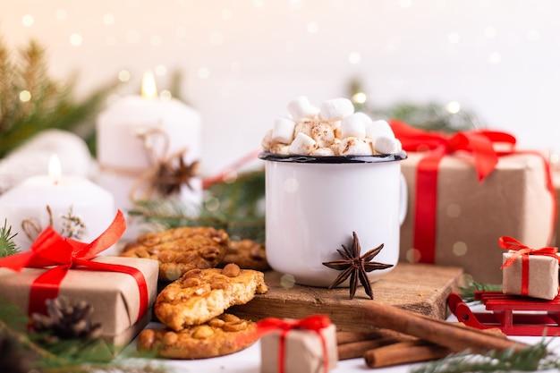 マシュマロとクッキーを添えたホットココアまたはコーヒーのエナメルカップ。木の枝、贈り物、燃えるろうそくの周り。クリスマスムード。はがきや冬の背景。 Premium写真