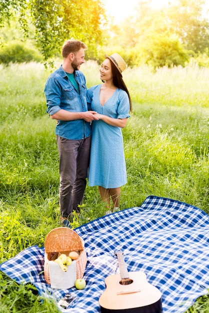 Enamored couple hugging standing by checkered plaid on picnic Free Photo