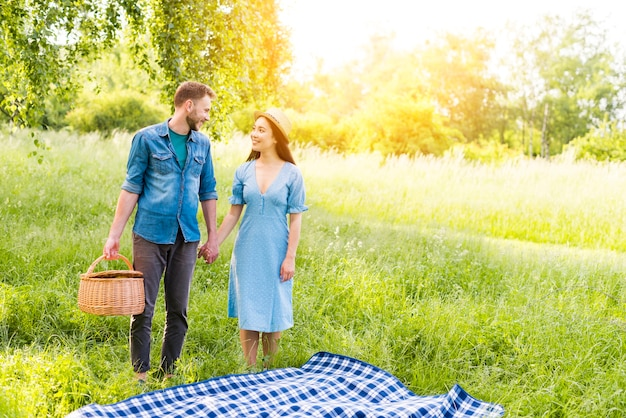 Enamored couple standing by checkered plaid holding hands in countryside Free Photo