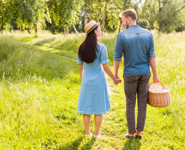 Enamored smiling couple standing on park path holding hands Free Photo