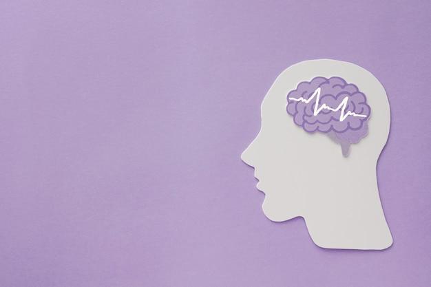 紫色の背景、てんかんとアルツハイマー病の認識、発作障害、精神的健康の概念に関する脳波脳紙カットアウト Premium写真