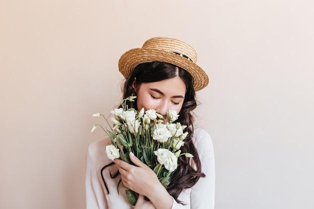 白い花を嗅ぐ魅惑的なアジアの女性。ベージュの背景に分離されたトルコギキョウと中国人女性のスタジオショット。 無料写真