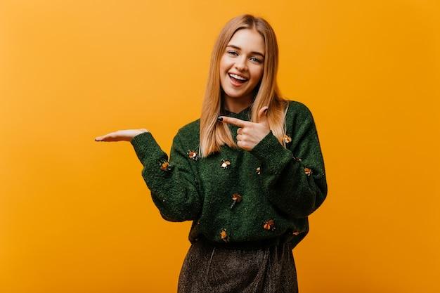 幸せを表現する流行のニットセーターで魅惑的な盲目の女性。オレンジ色の上に立っている魅力的なヨーロッパの女性の屋内の肖像画。 無料写真