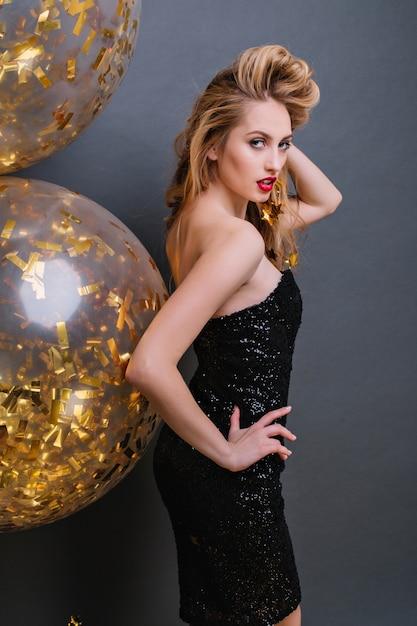 Incantevole ragazza bionda che guarda sopra la spalla e gioca con i suoi capelli durante il servizio fotografico della festa. slim bionda signora indossa un abito nero in posa con palloncini dorati. Foto Gratuite