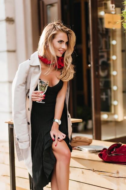 日焼けした肌で魅惑的な金髪の女性、グラスワインを持って笑っている。シャンパンを楽しんでいる黒のドレスとベージュのコートで興奮した金髪の女性の屋外の肖像画。 無料写真
