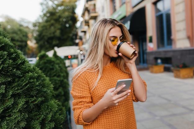 Incantevole giovane donna bionda in attesa di un messaggio telefonico mentre beve il caffè per strada Foto Gratuite
