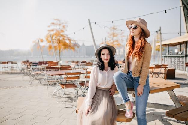 スタイリッシュな帽子をかぶった女性の友人と屋外カフェに座っている長いスカートの魅惑的なブルネットの女性 無料写真