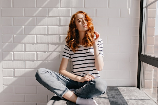 Enchanting curly female model sitting on window sill. enthusiastic caucasian girl in striped t-shirt posing with eyes closed. Free Photo