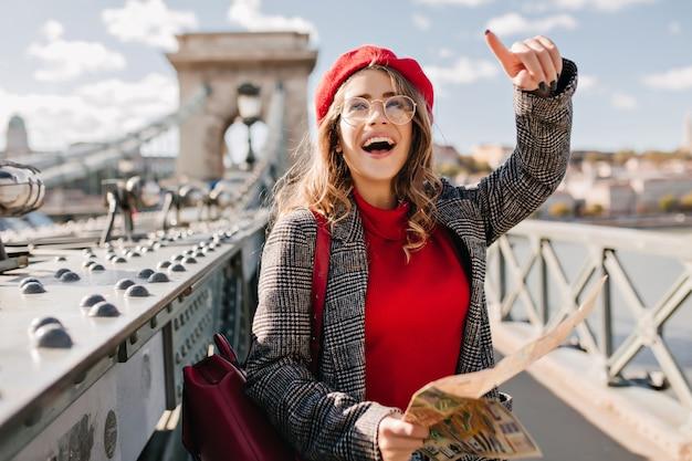Очаровательная туристка, изучающая францию с картой Бесплатные Фотографии
